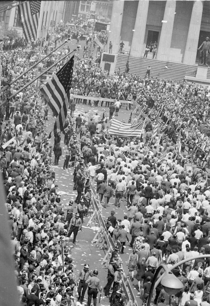 Description of  American flag-bearing construction workers, angered by Mayor John Lindsay's apparent anti-war sympathies, lead hundreds of New York City workers supporting U.S. war policy in Vietnam in a demonstration inside a barricaded area near Wall Street in lower Manhattan, May 12, 1970.  More than 1,000 police were on the scene to prevent possible clashes with anti-war student demonstrators, who were among office workers along the barricades.  (AP Photo)
