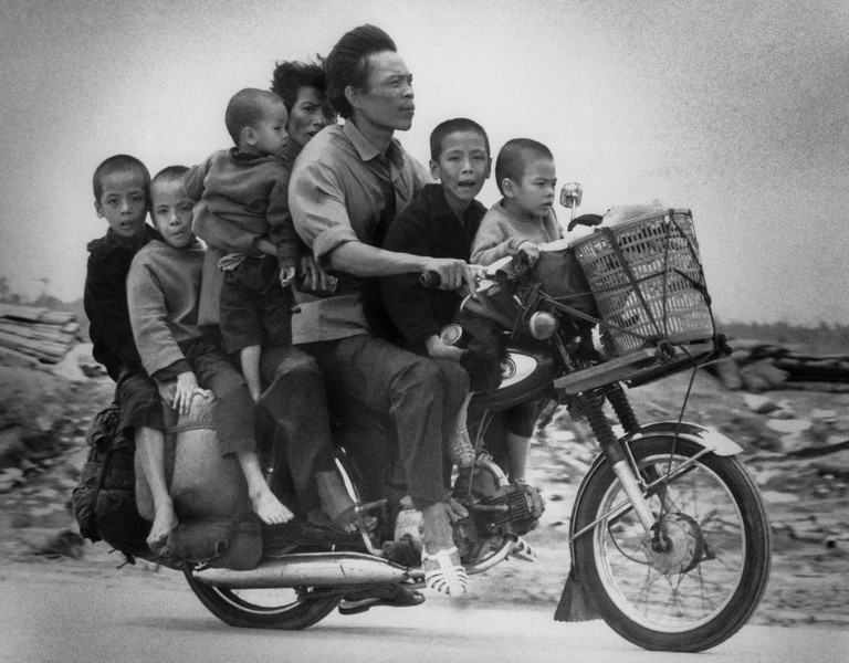 Description of  South Vietnamese parents, with their five children, ride along Highway 13, fleeing southwards from An Loc toward Saigon on June 19, 1972. (AP Photo/Nick Ut)