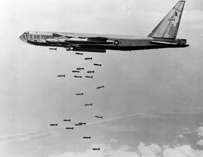 Description of  A U.S. B-52 stratofortress drops a load of 750-pounds bombs over a Vietnam coastal area during the Vietnam War, Nov. 5, 1965.  (AP Photo/USAF)