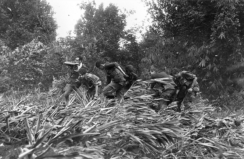 Description of  Photographer Larry Burrows, far left, struggles through elephant grass and the rotorwash of an American evacuation helicopter as he helps GIs to carry a wounded buddy on a stretcher from the jungle to the helicopter in Mimot, Cambodia, May 4, 1970.  The evacuation was during the U.S. incursion into Cambodia during the Vietnam War.  (AP Photo/Henri Huet)