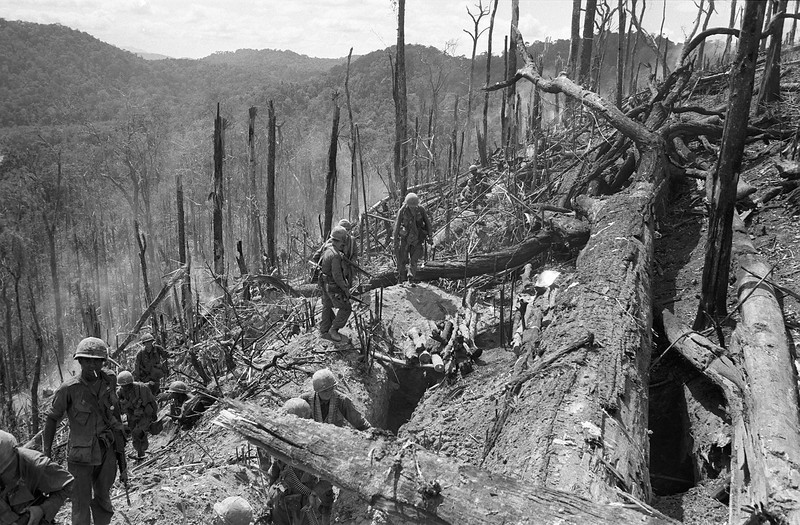 Description of  U.S. troops move toward the crest of Hill 875 at Dak To in November, 1967 after 21 days of fighting, during which at least 285 Americans were believed killed. The hill in the central highlands, of little apparent strategic value to the North Vietnamese, was nevertheless the focus of intense fighting and heavy losses to both sides. (AP Photo)