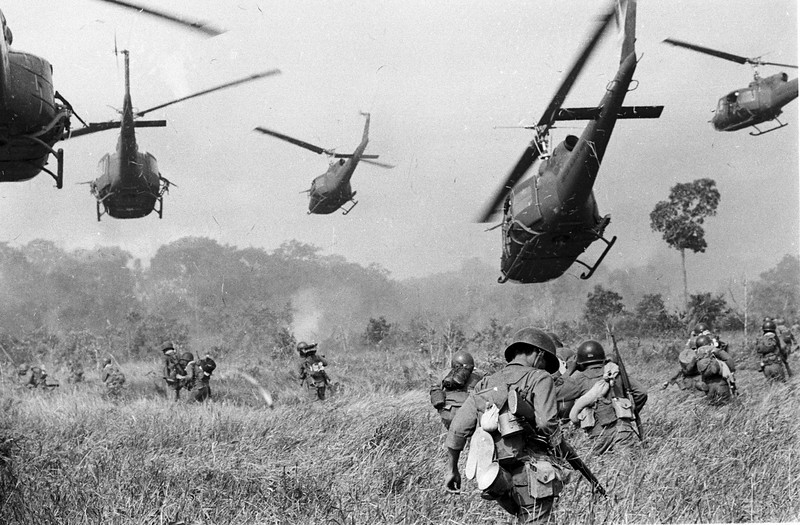 Description of  Hovering U.S. Army helicopters pour machine gun fire into a tree line to cover the advance of South Vietnamese ground troops in an attack on a Viet Cong camp 18 miles north of Tay Ninh, northwest of Saigon near the Cambodian border, in Vietnam in March of 1965. (AP Photo/Horst Faas, File)