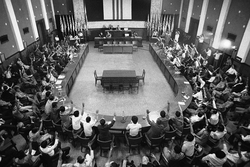 Description of  A joint session of South Vietnam's National Assembly votes on Sunday, April 28, 1975 to ask President Tran Van Huong to turn over his office to Gen. Duong Van Minh. The assembly made a move in the 11th hour to attempt to negotiate a settlement with the Communist forces. (AP Photo/Errington)