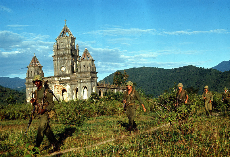 Description of  U.S. Marines pass a Catholic church as they patrol near Danang, Vietnam, during the Vietnam War in 1968.  (AP Photo)