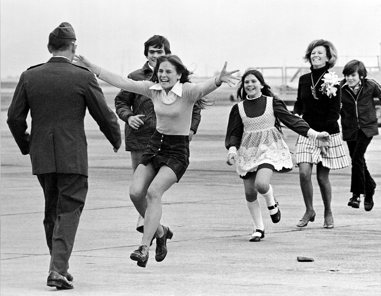 Description of  Released prisoner of war Lt. Col. Robert L. Stirm is greeted by his family at Travis Air Force Base in Fairfield, Calif., as he returns home from the Vietnam War, March 17, 1973. In the lead is Stirm's daughter Lorrie, 15, followed by son Robert, 14; daughter Cynthia, 11; wife Loretta and son Roger, 12. (AP Photo/Sal Veder)
