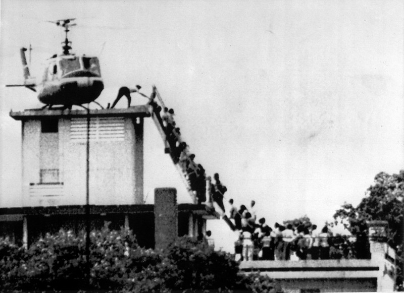Description of  Evacuees mount a staircase to board an American helicopter near the American Embasy in Saigon. (Hubert van Es/AFP/Getty Images)
