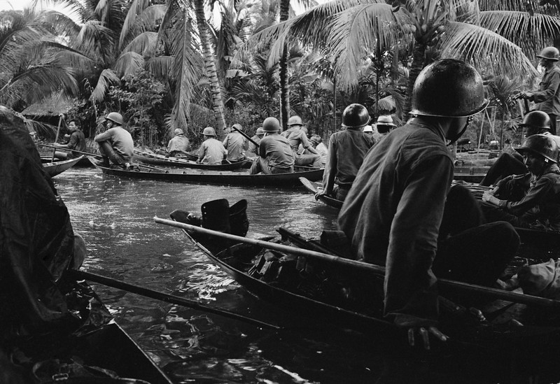 Description of  In a sudden monsoon rain, part of a company of about 130 South Vietnamese regional soldiers moves downriver in sampans during a dawn attack against a Viet Cong camp in the flooded Mekong Delta, about 13 miles northeast of Cantho, on Jan. 10, 1966. A handful of guerrillas were reported killed or wounded. (AP Photo/Henri Huet)