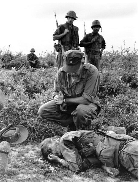 Description of  Chaplain John McNamara of Boston makes the sign of the cross as he administers the last rites to photographer Dickey Chapelle in South Vietnam Nov. 4, 1965. Chapelle was covering a U.S. Marine unit on a combat operation near Chu Lai for the National Observer when she was seriously wounded, along with four Marines, by an exploding mine. She died in a helicopter en route to a hospital. She became the first female war correspondent to be killed in Vietnam, as well as the first American female reporter to be killed in action. Her body was repatriated with an honor guard consisting of six Marines and she was given full Marine burial. (AP Photo/Henri Huet)