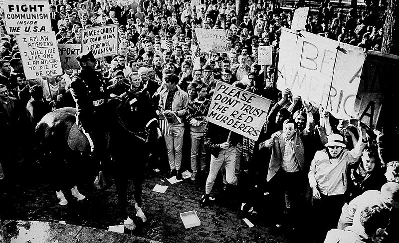 Description of  College students carrying pro-American signs heckle anti-war student demonstrators protesting U.S. involvement in Vietnam at the Boston Common in Boston, Ma., Oct. 16, 1965.  (AP Photo)