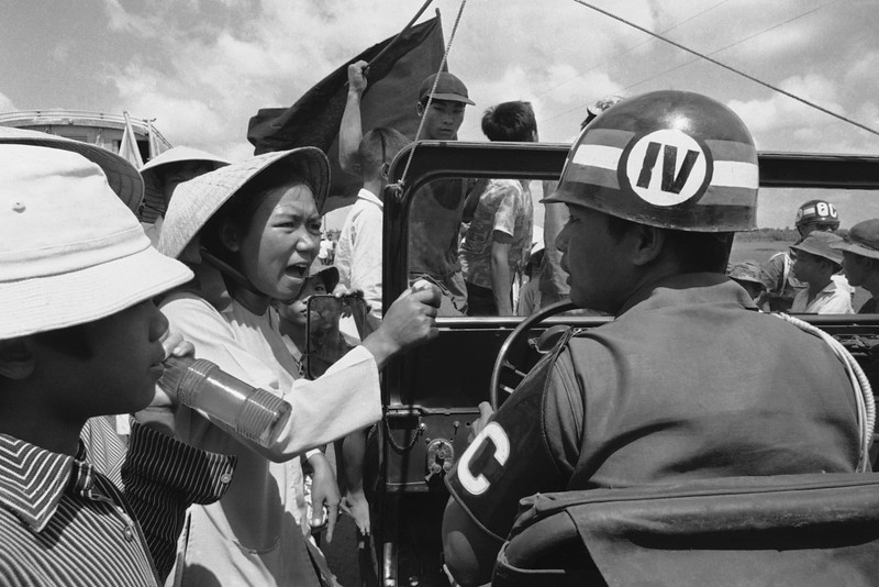 Description of  A woman villager holding a small rock yells at a South Vietnamese military policeman on Feb. 10, 1975 during a confrontation near Hoa Hao in the Western Mekong Delta in Vietnam. Villagers had erected barricades along the highway to protest a government order disbanding the private army of a Buddhist sect in the area. (AP Photo)