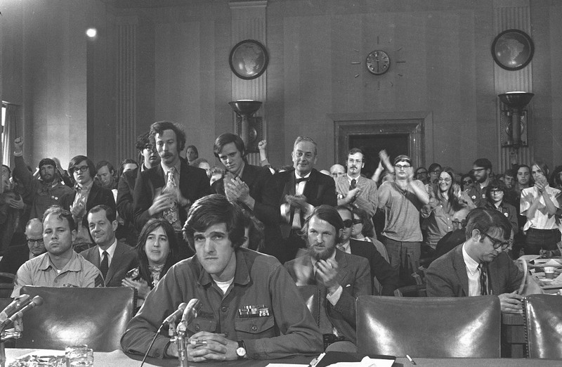 Description of  John Kerry, 27-year-old former navy lieutenant who heads the Vietnam Veterans Against the War (VVAW), receives support from a gallery of peace demonstrators and tourists as he testifies before the Senate Foreign Relations Committee in Washington, D.C., April 22, 1971.  (AP Photo/Henry Griffin)