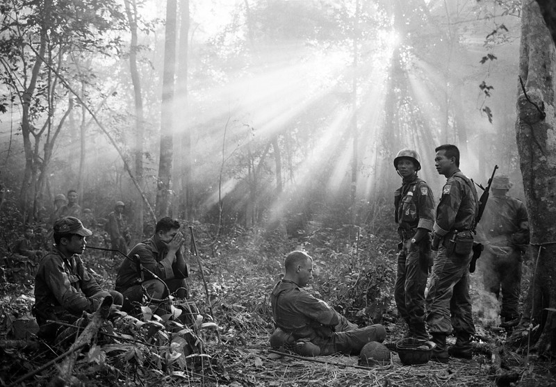 Description of  The sun breaks through the dense jungle foliage around the embattled town of Binh Gia, 40 miles east of Saigon, in early January 1965, as South Vietnamese troops, joined by U.S. advisors, rest after a cold, damp and tense night of waiting in an ambush position for a Viet Cong attack that didn't come. One hour later, as the possibility of an overnight attack by the Viet Cong diasappeared, the troops moved out for another long, hot day hunting the elusive communist guerrillas in the jungles. (AP Photo/Horst Faas)
