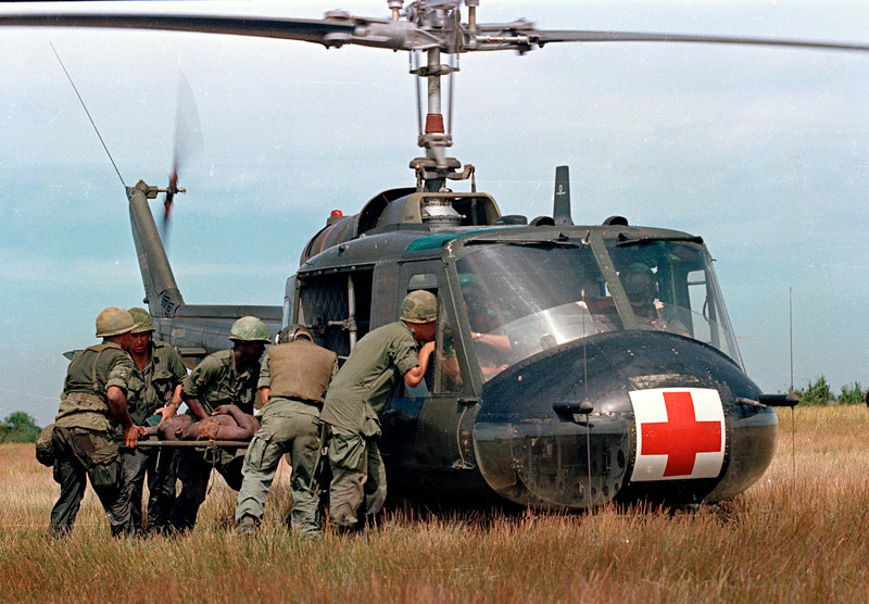 "Description of  A wounded member of the 1st Plt. Company ""C,"" 25th Infantry Division, is helped to a waiting UH-1D ""Iroquois"" helicopter in Vietnam, May 10, 1967, during the Vietnam War.  (AP Photo)"