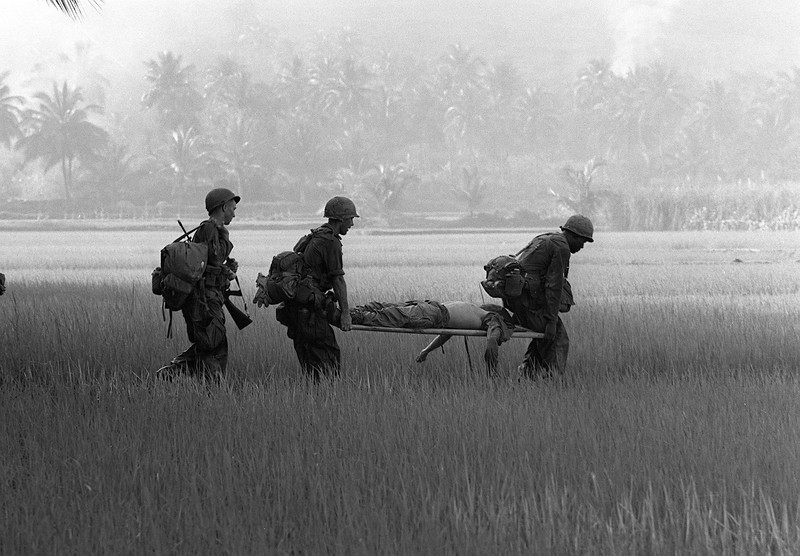 Description of  U.S. troops carry the body of a fellow soldier across a rice paddy for helicopter evacuation near Bong Son in early February 1966.  The soldier, a member of the 1st Air Cavalry Division, was killed during Operation Masher on South Vietnam's central coast.  (AP Photo/Rick Merron)