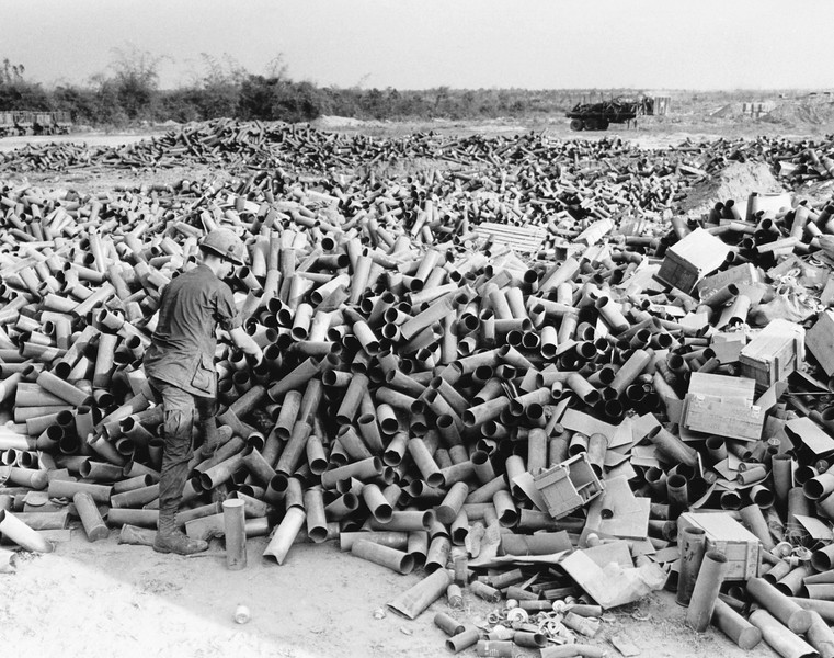 Description of  Empty artillery cartridges pile up at the artillery base at Soui Da, some 60 miles northwest of Saigon, at the southern edge of War Zone C, on March 8, 1967. (AP Photo/Horst Faas)