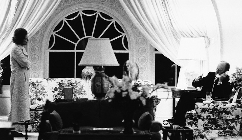 Description of  U.S. President Gerald Ford discusses the Vietnam evacuation of Americans by telephone with a senior aide while Mrs. Betty Ford looks on in the living quarters of the White House in a picture released by the White House, Tuesday, April 29, 1975 in Washington. (AP Photo)