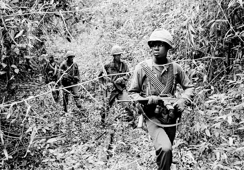 Description of  U.S. soldiers are on the search for Viet Cong hideouts in a swampy jungle creek bed, June 6, 1965, at Chutes de Trian, some 40 miles northeast of Saigon, South Vietnam.  (AP Photo/Horst Faas)