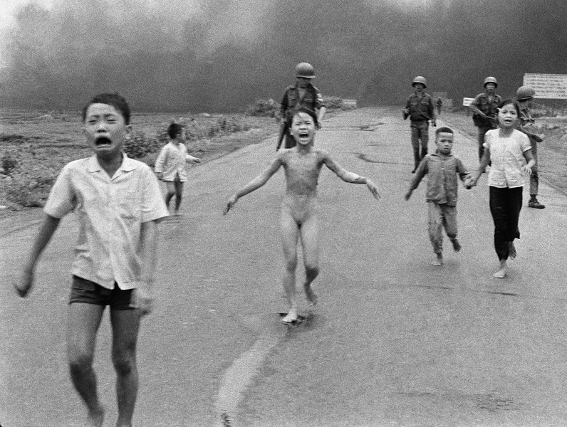 Description of  South Vietnamese forces follow after terrified children, including 9-year-old  Kim Phuc, center, as they run down Route 1 near Trang Bang after an aerial napalm attack on suspected Viet Cong hiding places on June 8, 1972.  A South Vietnamese plane accidentally dropped its flaming napalm on South Vietnamese troops and civilians. The terrified girl had ripped off her burning clothes while fleeing. The children from left to right are: Phan Thanh Tam, younger brother of Kim Phuc, who lost an eye, Phan Thanh Phouc, youngest brother of Kim Phuc, Kim Phuc, and Kim's cousins Ho Van Bon, and Ho Thi Ting.  Behind them are soldiers of the Vietnam Army 25th Division. (AP Photo/Nick Ut)