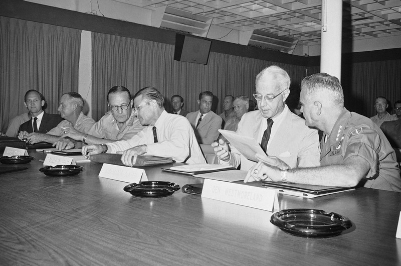 Description of  Secretary of Defense Robert S. McNamara (second from left), and Gen Earle Wheeler, chairman of the Joint Chiefs of Staff, huddle in one corner while Ellsworth Bunker, U.S. Ambassador to South Vietnam (second from right), and Gen. William C. Westmoreland, right, commander of U.S. Forces in Vietnam, go over a report at the beginning of briefings for the secretary at U.S. Army Headquarters on Tan Son Nhut Air Base, Friday, July 6, 1967 in Saigon. (AP Photo/Cung)