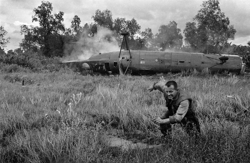 Description of  A U.S. crewman runs from a crashed CH-21 Shawnee troop helicopter near the village of Ca Mau in the southern tip of South Vietnam, Dec. 11, 1962. Two helicopters crashed without serious injuries during a government raid on the Viet Cong-infiltrated area. Both helicopters were destroyed to keep them out of enemy hands. (AP Photo/Horst Faas)