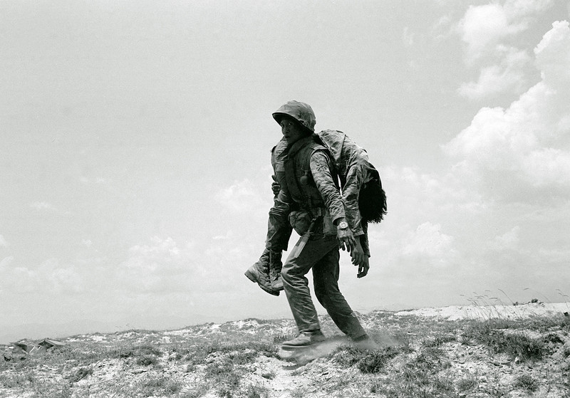 Description of  A South Vietnamese Marine carries the dead body of a comrade killed on Route 1, about seven miles south of Quang Tri Sunday, April 30, 1972. Marines were fighting to reopen the road in order to break the North Vietnamese siege of the provincial capital. (AP Photo/Koichiro Morita)