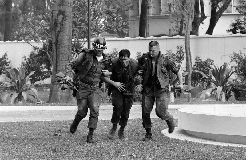 Description of  Two U.S. military policemen aid a wounded fellow MP during fighting in the U.S. Embassy compound in Saigon, Jan. 31, 1968, at the beginning of the Tet Offensive. A Viet Cong suicide squad seized control of part of the compound and held it for about six hours before they were killed or captured. (AP Photo/Hong Seong-Chan)