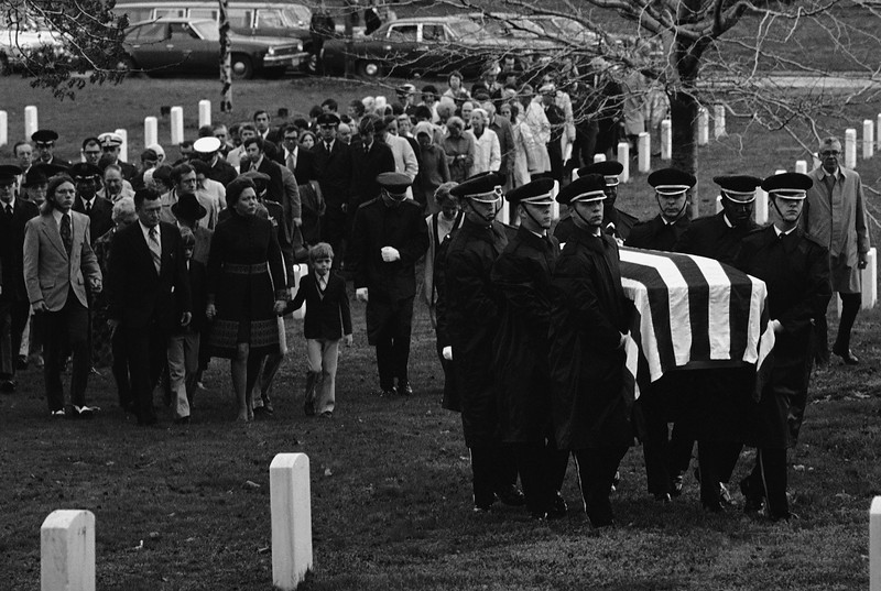 Description of  Mrs. Evelyn Grubb, of Colonial Heights, Va., left, follows her husband Wilmers coffin at Arlington National Cemetery, Thursday, April 4, 1974, Washington, D.C. Col. Grubb's name was released by the Democratic Republic of Vietnam as one of the prisoners of war who died in captivity. Mrs. Grubb holds the hands of two of her sons, Roy, 7, right, and Stephen, 10. The rest of the group is unidentified. (AP Photo/Henry Burroughs)