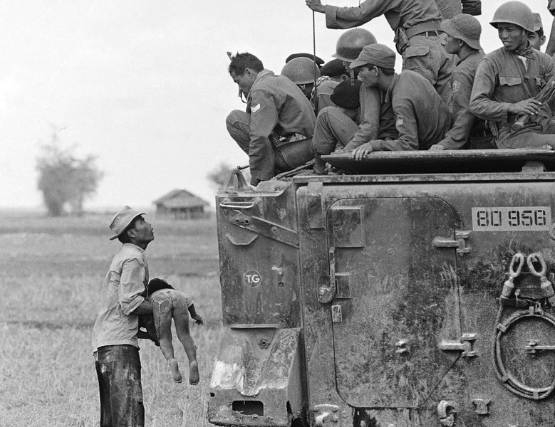 Description of  A father holds the body of his child as South Vietnamese Army Rangers look down from their armored vehicle March 19, 1964.  The child was killed as government forces pursued guerrillas into a village near the Cambodian border.  (AP Photo/Horst Faas)