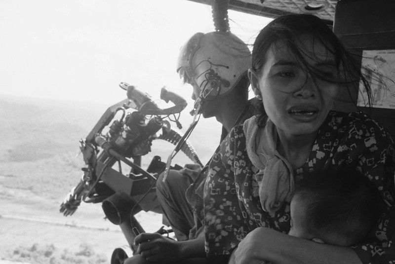 Description of  A refugee clutches her baby as a government helicopter gunship carries them away near Tuy Hoa, 235 miles northeast of Saigon on March 22, 1975. They were among thousands fleeing from Communist advances. (AP Photo/ Nick Ut)