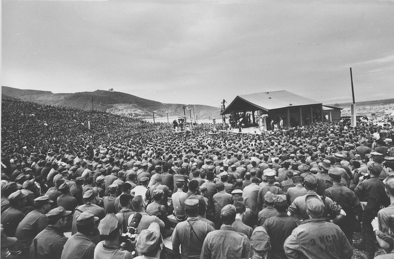 "Description of  More than 12,000 U.S. Marines crowd into an outdoor amphitheater to watch comedian Bob Hope and Phil Crosby open Hope's USO Christmas Show tour at Da Nang, Vietnam, with Raquel Welch and singer Barbara McNair, left, Dec. 19, 1967.  Crosby, wearing a wig, carries a ""Make Love Not War"" sign.  (AP Photo)"