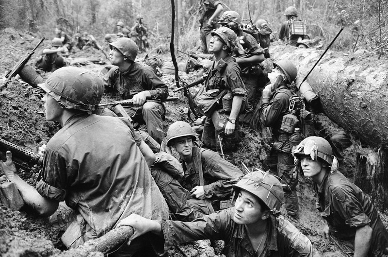 Description of  American infantrymen crowd into a mud-filled bomb crater and look up at tall jungle trees seeking out Viet Cong snipers firing at them during a battle in Phuoc Vinh, north-Northeast of Saigon in Vietnam's War Zone D on June 15, 1967. (AP Photo/Henri Huet, File)