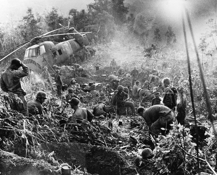 Description of  Weary after a third night of fighting against North Vietnamese troops, U.S. Marines crawl from foxholes located south of the demilitarized zone (DMZ) in Vietnam, 1966. The helicopter at left was shot down when it came in to resupply the unit. (AP Photo/Henri Huet)