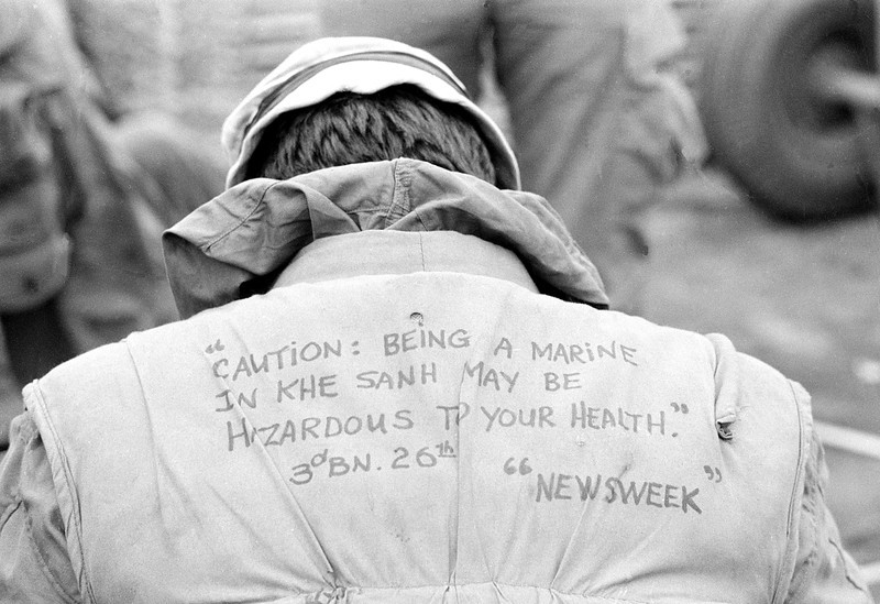 "Description of  A U.S. Marine shows a message written on the back of his flack vest at the Khe Sanh combat base in Vietnam on Feb. 21, 1968 during the Vietnam War.  The quote reads, ""Caution:  Being a Marine in Khe Sanh may be hazardous to your health.""  Khe Sanh had been subject to increased rocket and artillery attacks from the North Vietnamese troops in the area.  (AP Photo/Rick Merron)"