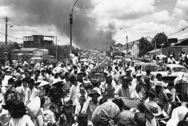 Description of  Smoke rises from the southwestern part of Saigon on May 7, 1968 as residents stream across a bridge leaving the capital to escape heavy fighting between the Viet Cong and South Vietnamese soldiers. (AP Photo)