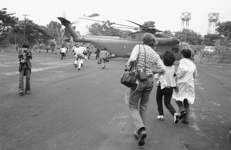 Description of  Americans and Vietnamese run for a U.S. Marine helicopter in Saigon during the evacuation of the city, April 29, 1975. (AP Photo)