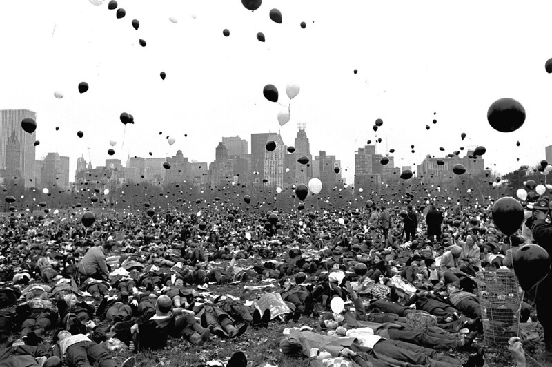 Description of  Supporters of the Vietnam moratorium lie in the Sheep Meadow of New York's Central Park Nov. 14, 1969 as hundreds of black and white balloons float skyward. A spokesman for the moratorium committee said the black balloons represented Americans who died in Vietnam under the Nixon administration, and the white balloons symbolized the number of Americans who would die if the war continued.  (AP Photo/J. Spencer Jones)