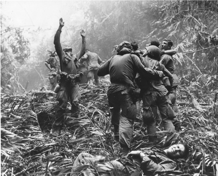 Description of  As fellow troopers aid wounded buddies, a paratrooper of A Company, 101st Airborne, guides a medical evacuation helicopter through the jungle foliage to pick up casualties during a five-day patrol of Hue, South Vietnam, in April, 1968. (AP Photo/Art Greenspon)