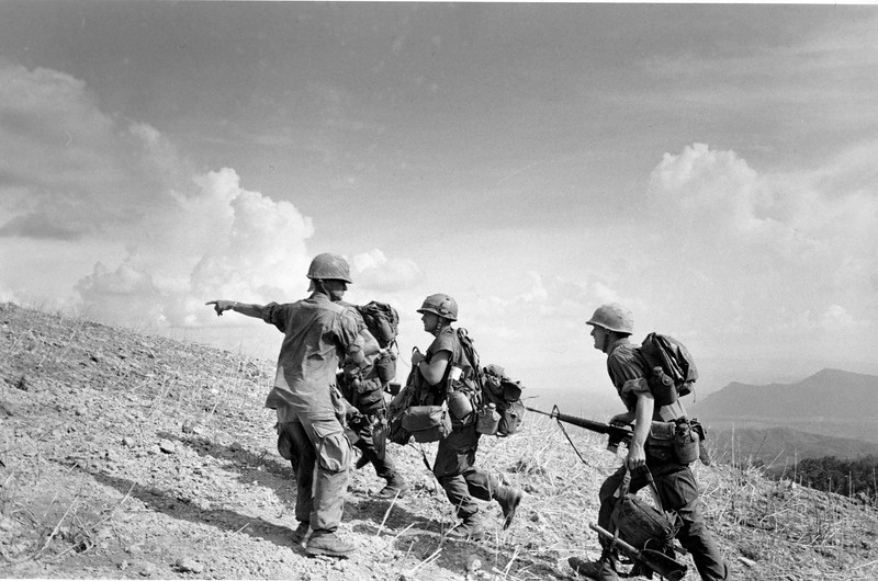 Description of  A U.S. Marine sergeant points directions to a group of newly arrived replacement soldiers atop embattled Hill 881, below the demilitarized zone near the Laotian border, South Vietnam, in May 1967. The men were flown in by helicopter to enforce U.S. Marine lines badly weakened by casualties after several days of fighting for the strategic hills. (AP Photo)