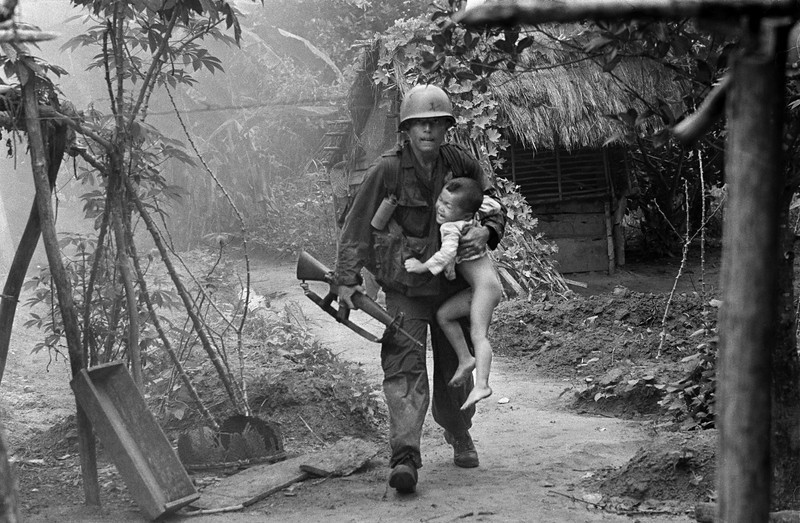 Description of  A U.S. infantryman from A Company, 1st Battalion, 16th Infantry  carries a crying child from Cam Xe village after dropping a phosphorous grenade into a bunker cleared of civilians during an operation near the Michelin rubber plantation northwest of Saigon, August 22, 1966. A platoon of the 1st Infantry Division raided the village, looking for snipers that had inflicted casualties on the platoon. GIs rushed about 40 civilians out of the village before artillery bombardment ensued. (AP Photo/Horst Faas)