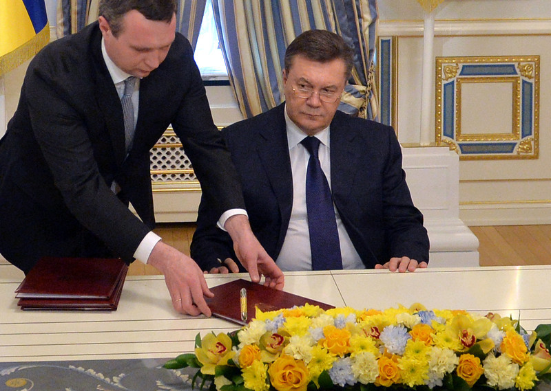 Description of  Ukrainian President Viktor Yanukovych signs an agreement with the opposition on February 21, 2014. Ukraine's leader and opposition on Friday signed a deal to end the splintered country's worst crisis since independence after three days of carnage left nearly 100 protesters dead and the heart of Kiev resembling a war zone. President Viktor Yanukovych's dramatic decision to hold early elections and form a new unity government was met with caution by the tens of thousands gathered on central Kiev's main square for a protest that began exactly three months earlier. SERGEI SUPINSKY/AFP/Getty Images