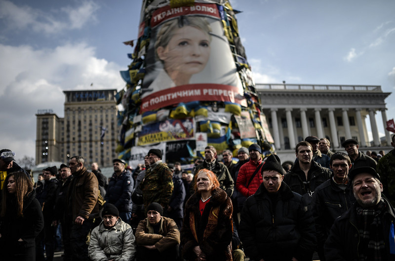 Description of  Anti-government protesters stand beneath a giant poster of jailed former Ukrainian Prime minister Yulia Tymoshenko as they attend a rally on Independence square in Kiev on February 21, 2014. Ukrainian President Viktor Yanukovych and three main opposition leaders signed a deal on February 21 to end a three-month crisis over the ex-Soviet country's political future that has led to nearly 100 deaths. The pact paving the way for early elections and a shift in political power toward parliament was signed in the Blue Hall of the presidential palace in the presence of three EU envoys, an AFP correspondent said. BULENT KILIC/AFP/Getty Images