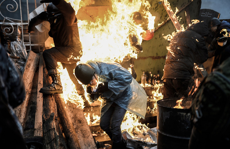"Description of  Protesters burn as they stand behind burning barricades during clashes with police on February 20, 2014 in Kiev. Ukraine's embattled leader announced a ""truce"" with the opposition as he prepared to get grilled by visiting EU diplomats over clashes that killed 26 and left the government facing diplomatic isolation. The shocking scale of the violence three months into the crisis brought expressions of grave concern from the West and condemnation of an ""attempted coup"" by the Kremlin.   (BULENT KILIC/AFP/Getty Images)"