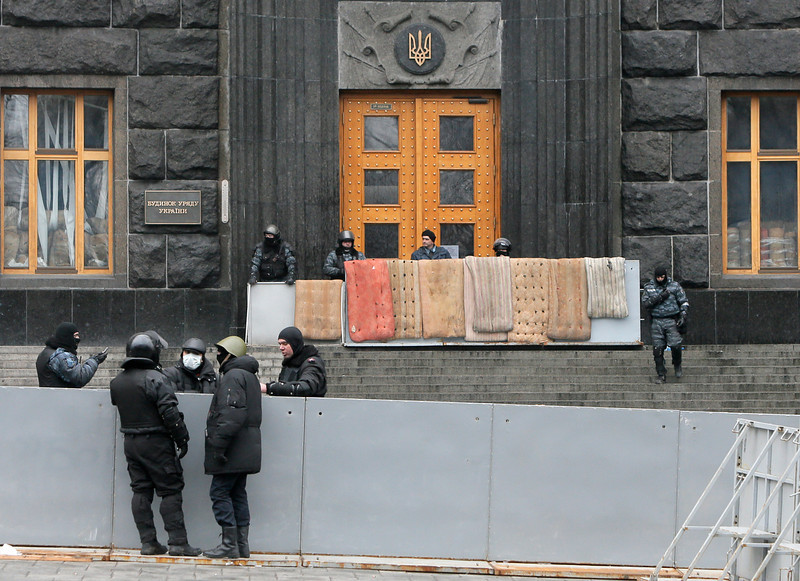 Description of  Police officers block the entrance to the Cabinet of Ministers in the center of Kiev, Ukraine, Thursday, Feb. 20, 2014. Fierce clashes between police and protesters, some including gunfire, shattered a brief truce in Ukraine's besieged capital Thursday, killing numerous people. The deaths came in a new eruption of violence just hours after the country's embattled president and the opposition leaders demanding his resignation called for a truce and negotiations to try to resolve Ukraine's political crisis. (AP Photo/Efrem Lukatsky)