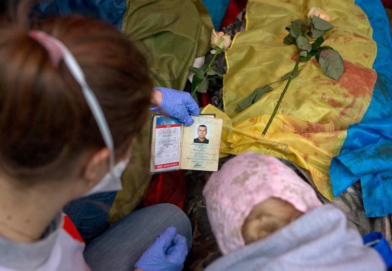 Description of  Paramedic look at the identification document of a killed anti-government protester, in central Kiev, Ukraine, Thursday, Feb. 20, 2014. A brief truce in Ukraine's embattled capital failed Thursday, spiraling into fierce clashes between police and anti-government protesters. (AP Photo/Darko Bandic)