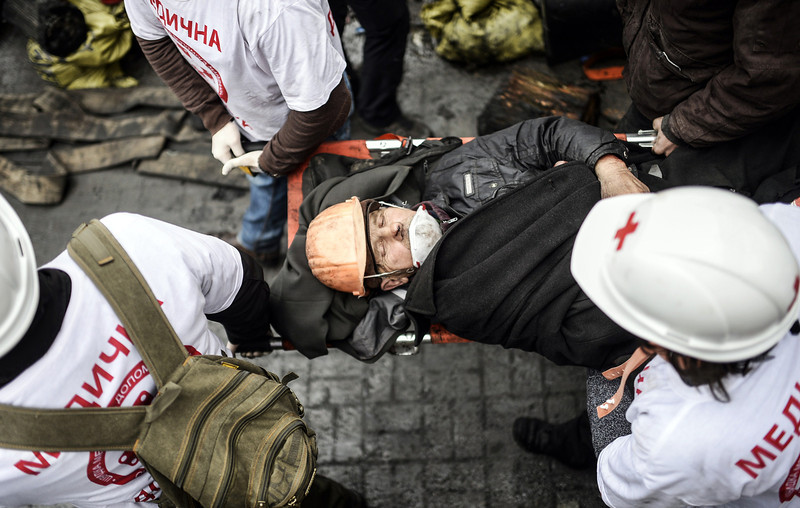Description of  Paramedics carry a protester wounded during clashes with riot police in central Kiev on February 20, 2014. Anti-government protesters take cover while under fire from police snipers during clashes with riot police in central Kiev on February 20, 2014. At least 25 protesters were killed on February 20 in fresh clashes between thousands of demonstrators and heavily-armed riot police in the heart of Kiev, AFP correspondents at the scene said. The bodies of eight demonstrators were lying outside Kiev's main post office on Independence Square, an AFP reporter said. The bodies of 17 other demonstrators with apparent gunshot wounds were also seen in the vicinity of two hotels on opposite sides of the protest encampment.  (BULENT KILIC/AFP/Getty Images)