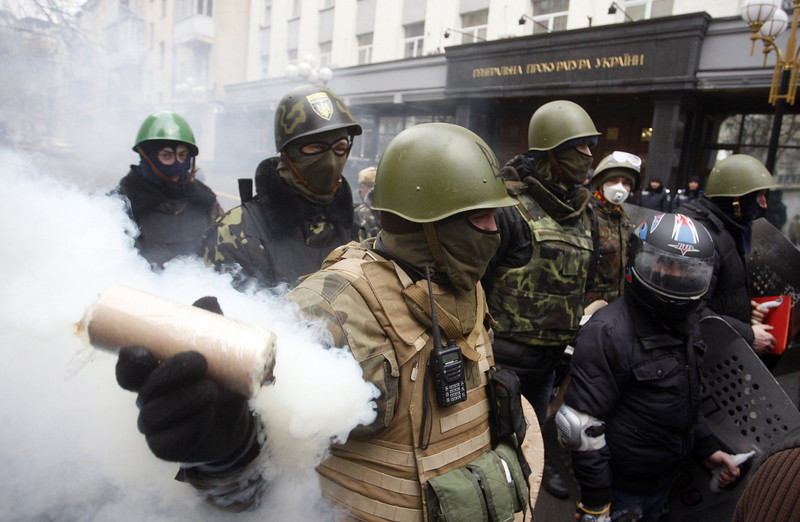 Description of  A man holds a smoke bomb as anti-government protestors take part in a protest rally in front of the Prosecutor General building in Kiev on February 14, 2014. Protesters armed with shields and clubs demanded the government stop prosecuting cases against anti-government activists involved in clashes with police.  (YURY KIRNICHNY/AFP/Getty Images)
