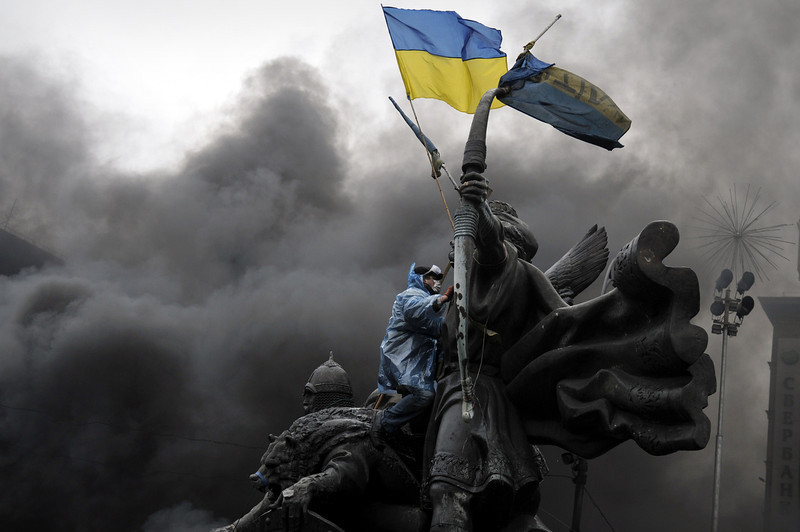 Description of  An anti-government protester sits on the Founders of Kiev monument during clashes with riot police in central Kiev on February 20, 2014. At least 25 protesters were killed on February 20 in fresh clashes between thousands of demonstrators and heavily-armed riot police in the heart of Kiev, AFP correspondents at the scene said. The bodies of eight demonstrators were lying outside Kiev's main post office on Independence Square, an AFP reporter said. The bodies of 17 other demonstrators with apparent gunshot wounds were also seen in the vicinity of two hotels on opposite sides of the protest encampment. (LOUISA GOULIAMAKI/AFP/Getty Images)