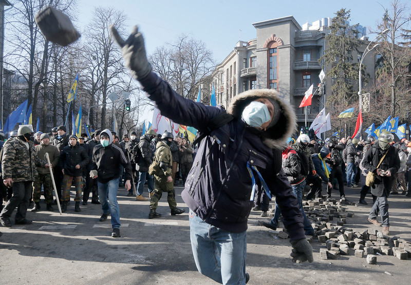 Description of  An anti-government protester  throw a stone during clashes with riot police outside Ukraine's parliament in Kiev, Ukraine, Tuesday, Feb. 18, 2014. Thousands of angry anti-government protesters clashed with police in a new eruption of violence following new maneuvering by Russia and the European Union to gain influence over this former Soviet republic. (AP Photo/Efrem Lukatsky)
