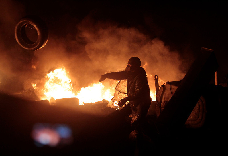 "Description of  Anti-government protesters clash with riot police in Kiev's Independence Square, the epicenter of the country's current unrest, in Ukraine, Thursday, Feb. 20, 2014. Ukraine's protest leaders and the president they aim to oust called a truce Wednesday, just hours after the military raised fears of a widespread crackdown with a vow to defeat ""terrorists"" responsible for seizing weapons and burning down buildings. (AP Photo/Sergei Chuzavkov)"