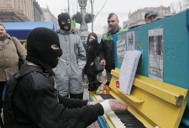 Description of  A protester in a balaclava and a flak jacket plays the piano in Kiev's Independence Square, the epicenter of the country's current unrest, Ukraine, Friday, Feb. 14, 2014. A Ukrainian opposition group says that all the protesters detained during nearly three months of opposition demonstrations have been released under an amnesty law. (AP Photo/Efrem Lukatsky)